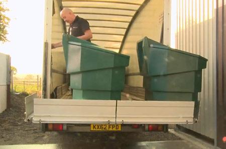 a photo of a man carefully loading a Bulk Bin into a van
