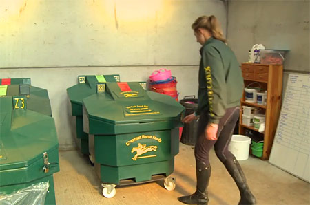 a photo of a woman opening a Bulk Bin for her horse